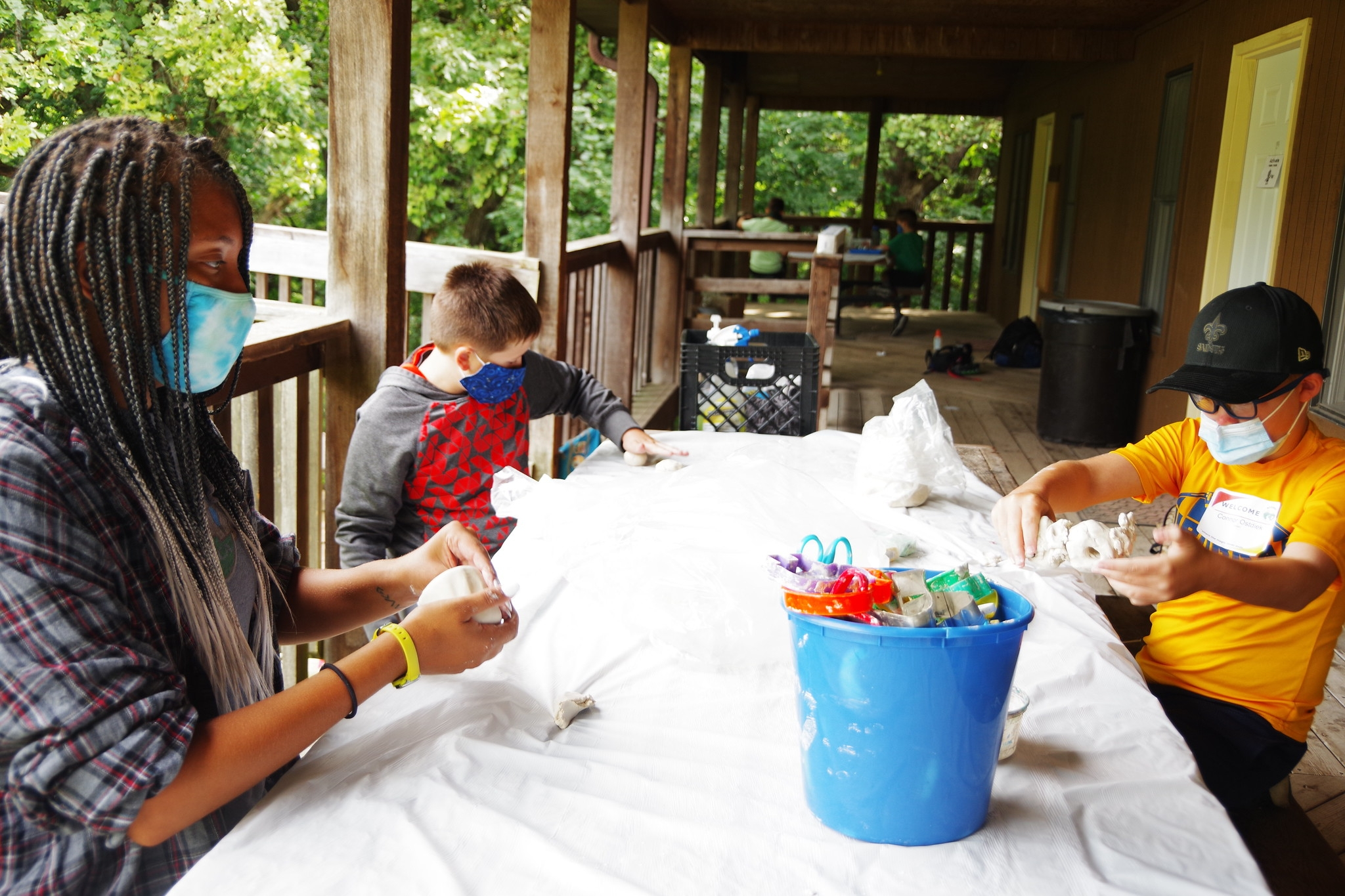 A counselor and two campers play with clay outside while wearing masks