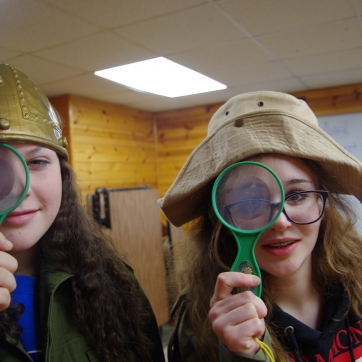 Two campers in costumes hold up magnifying glasses to their eyes.
