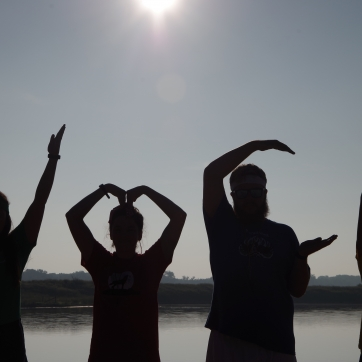 Four people make the letters YMCA with their arms as silhouettes in front of the camp lake