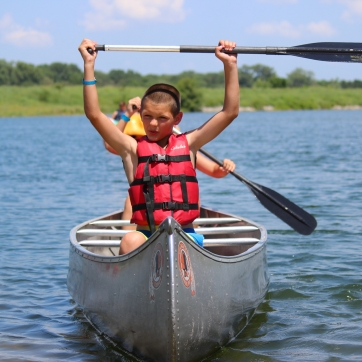 A camper sits at the front of a canoe and holds his paddle over his head in triumph