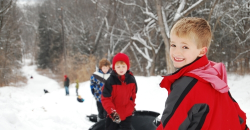A young boy smiles over his shoulder at the top of a sled hill