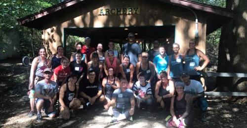 Participants in Adult Fitness adventure pose in front of the archery shed