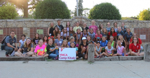 Participants in Camp Kitaki's ranch camp pose in front of the brick wall at camp