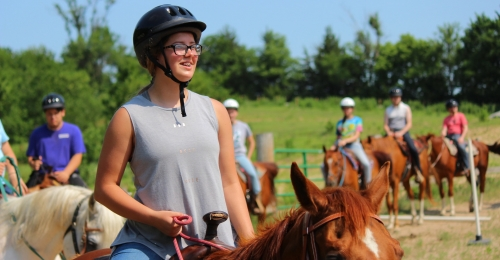 A camper with glasses on horseback smiles while other campers on horseback follow her lead.