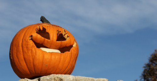 A jack o lantern smiles on top of a rock wall in front of a blue sky
